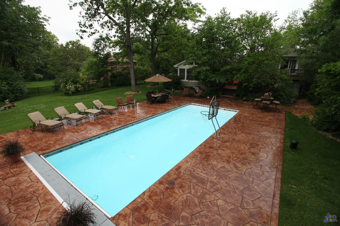 Oceanside fiberglass pool with deck jets stamped and stained concrete deck jets and basketball set