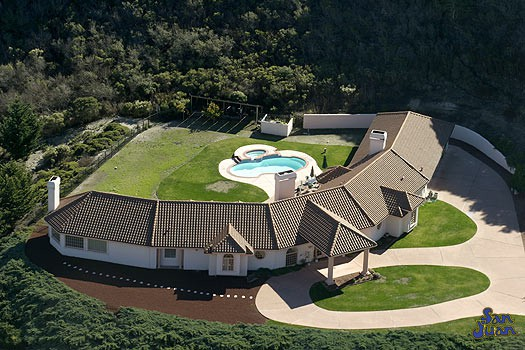 atlantic pool shape behind large curved house in large field