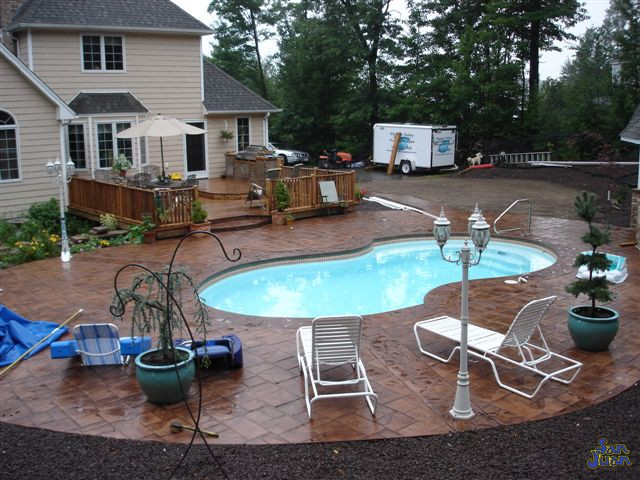 bayside fiberglass pool with travertine pavers