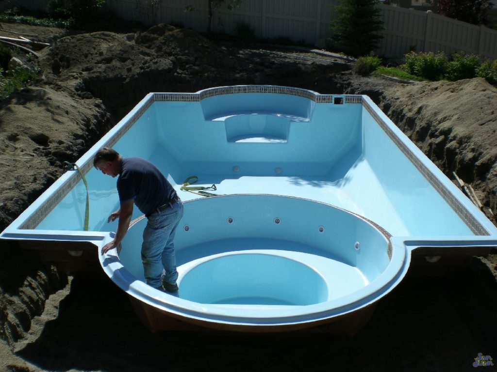 fiberglass pool being installed - includes spa in the same body as pool