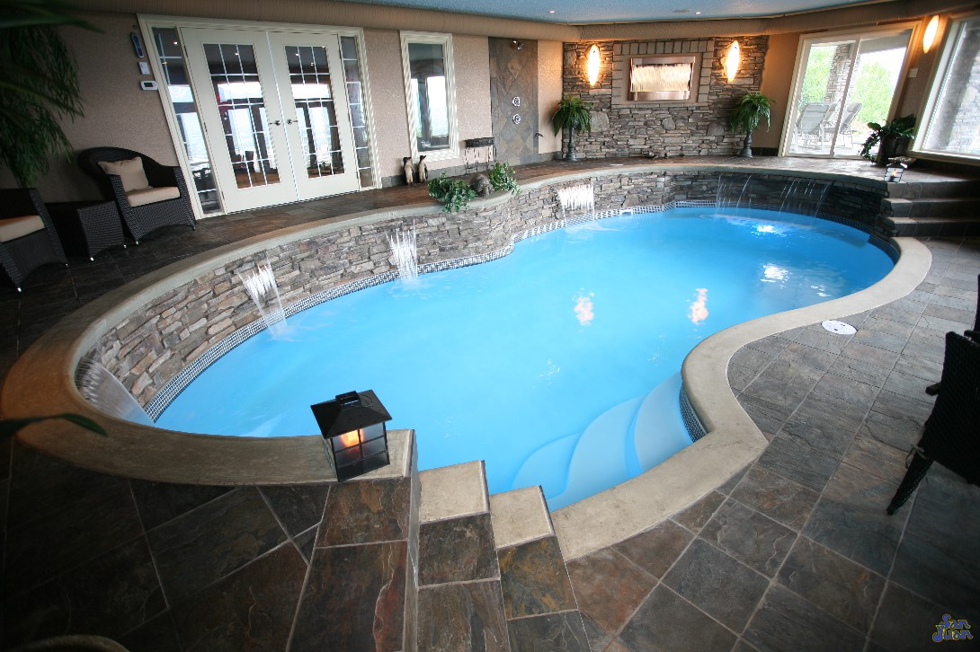 fiberglass pool installed inside home with waterfalls