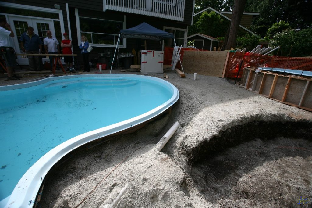 installing a fiberglass pool before pouring concrete