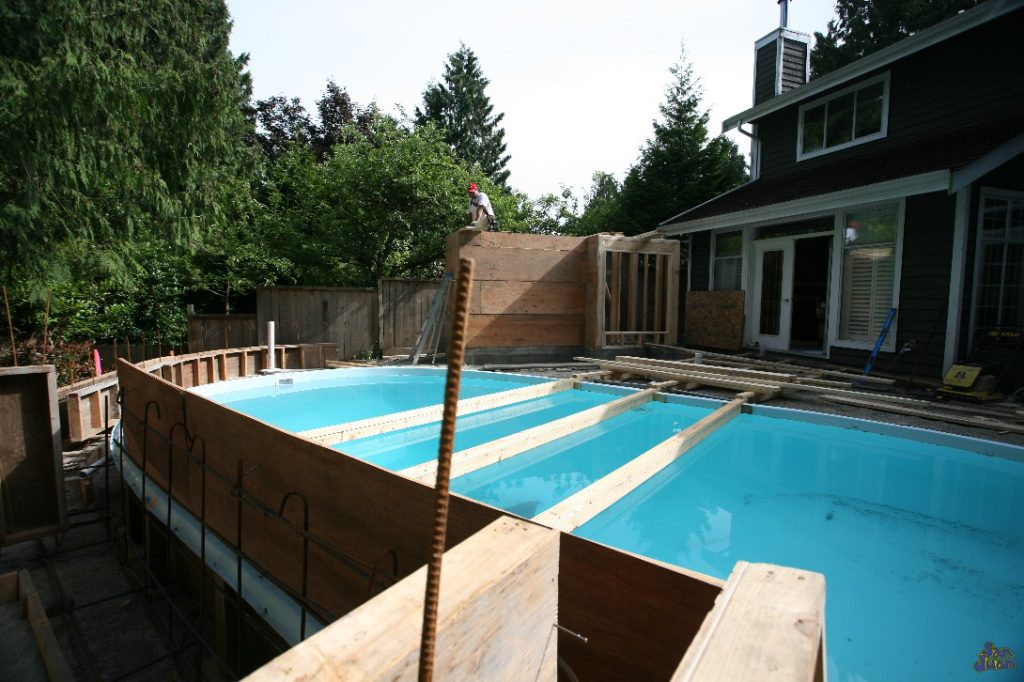installing forms and pouring concrete around fiberglass pool