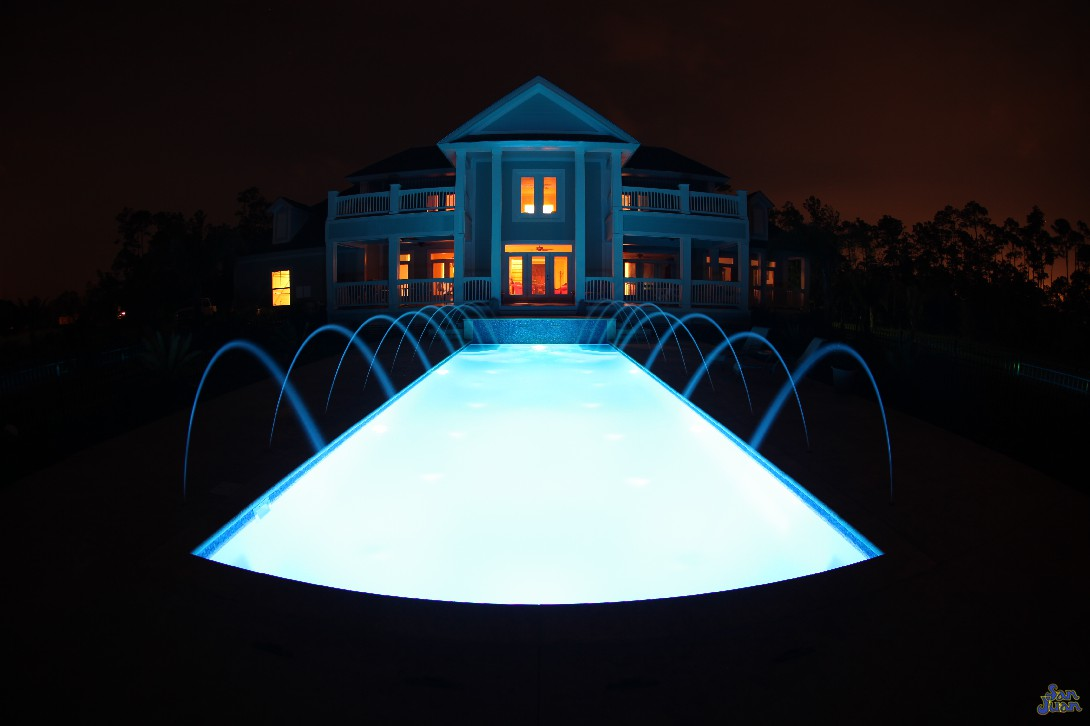 luxor deep fiberglass pool with raised tile wall and deck jets at night with LED lighting