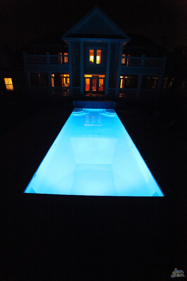 luxor deep fiberglass pool with raised tile wall at night with LED lighting