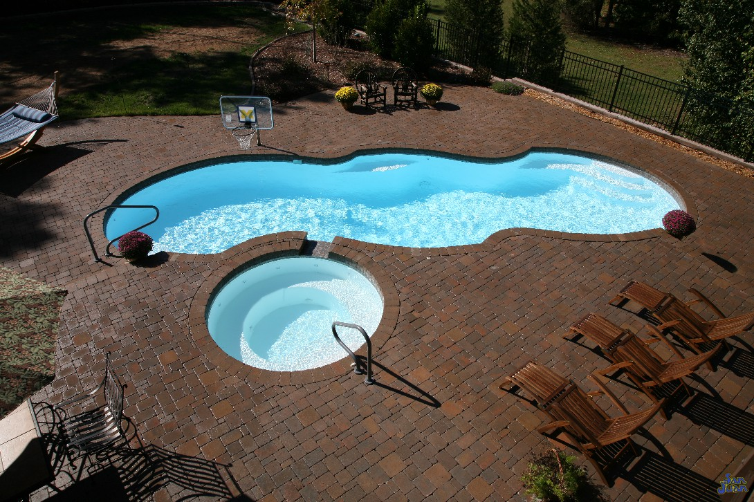 mirage pool shape with brick pavers handrails basketball goal and raised spa