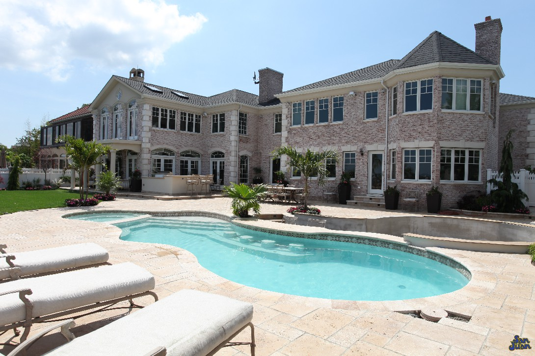 pleasure island fiberglass pool shape with attached spa located next to a lake and large house