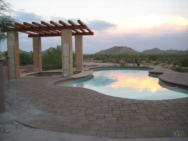 pleasure island fiberglass pool shape with stone pergola and sunset