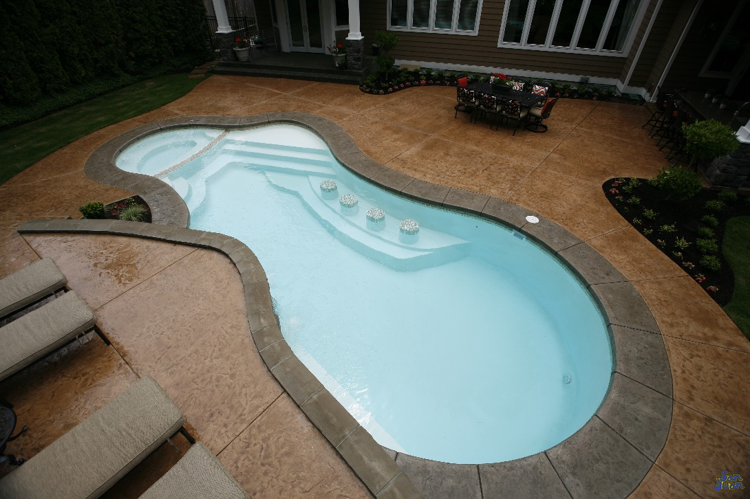 pleasure island fiberglass pool with attached spa bar seating and stamped stained concrete (2)