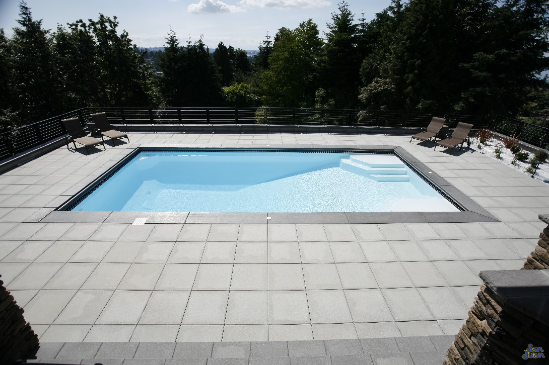 This image does a great job of illustrating the variability of this swimming pool. You can see just how quickly the shallow end gives way to the deep end basin. It also elegantly displays the beauty of this swimming pool when paired with a modern design - such as this square pattern travertine decking.