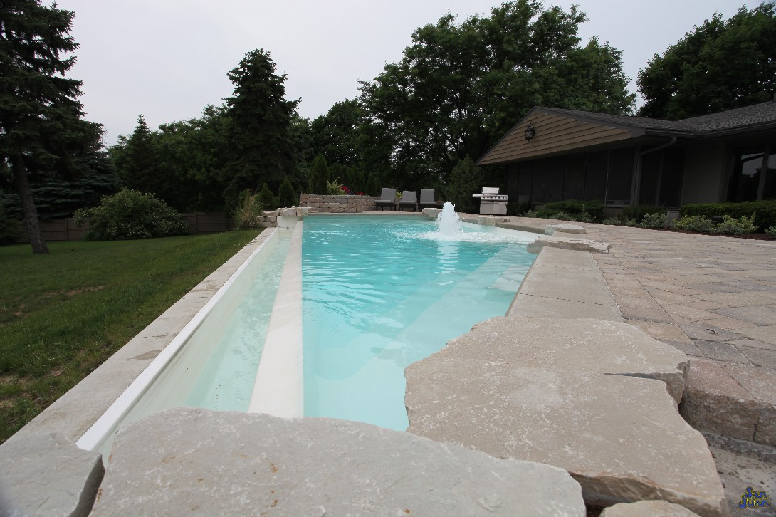 A splash pad bubbler, negative edge waterfall, sharp corners and swim up seating - what else can this amazing pool offer? We give you all of the fun design options up front so you don't have to think of new ways to spiff up your pool. We like to be turn-key like that. You give us the call, we bring the fun, and summer commences!