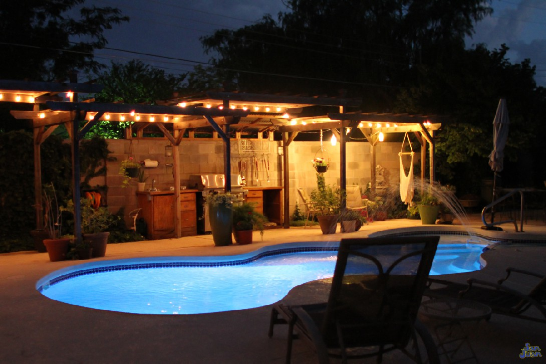 Here is another view of this gorgeous swimming pool at night with all illumination turned on. You can see how adding a little landscaping can really boost the beauty of your overall backyard experience. We can help you with these design approaches if you're looking for ways to achieve the same look.