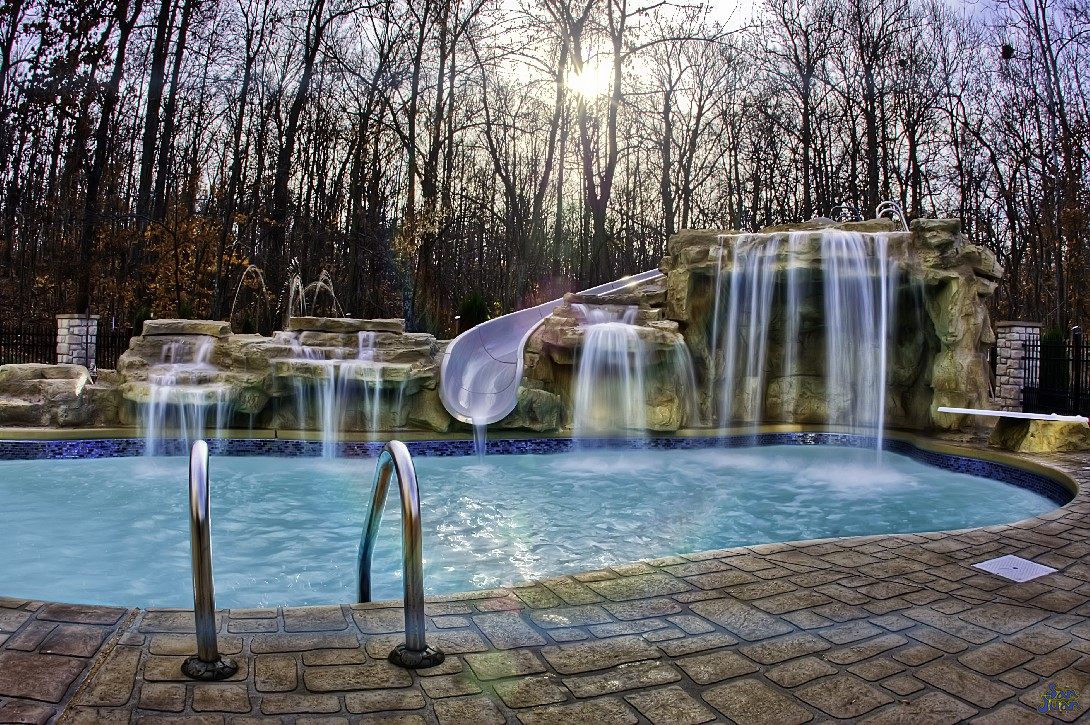 Wow! That's a stunning view! We love looking at amazing pictures like this because it reminds us and our customers that this is achievable for your own backyard! What we're looking at here is a pair of raised grotto waterfalls tied into a secondary water feature pump. It's simple enough in design but absolutely gorgeous to look at!