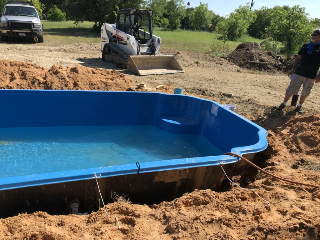 "We over dig our pool shell by 12""-24"". This leaves our crews plenty of room to get beneath the structure and plumb our return lines & lighting."