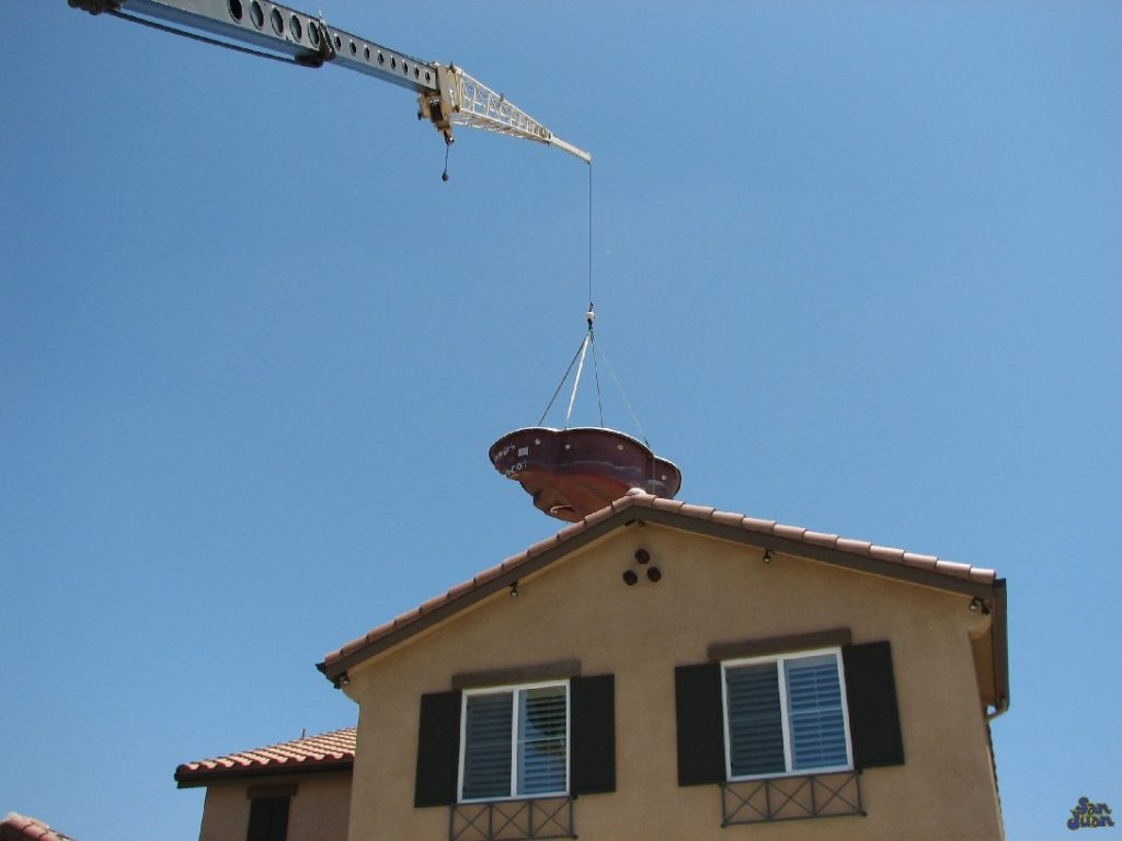 Did you not believe us when we said we could install this pool nearly anywhere? Ever wonder how we do it? This picture is a perfect testimony of our ability to literally lift our products right over your house. Once hooked up to a crane, we can literally lift and lower our pool and spas right into your backyard!