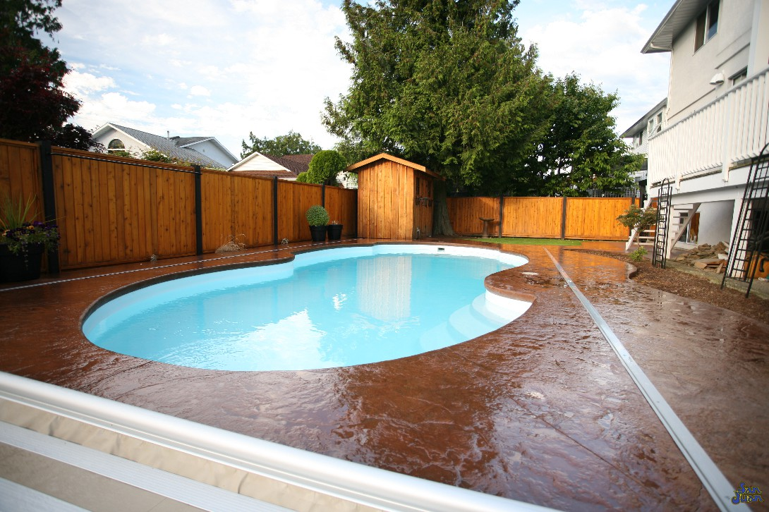 atlantic deep end pool shape with stamped stained concrete and wooden fence