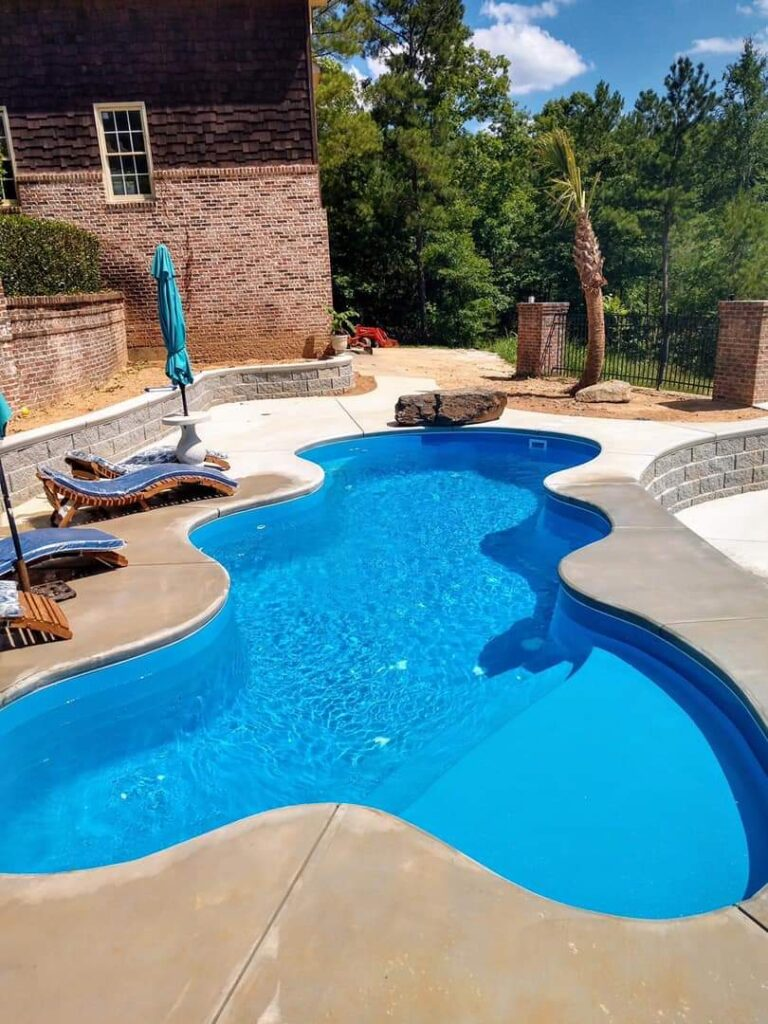 """The Desert Falls is a relaxing, free form swimming pool with a wide tanning ledge and lots of curves! This fiberglass swimming pool provides the user with an overall length of 28' 9.75"""" and width of 12' 11"""". Tucked snugly into any Medium Sized backyard, this swimming pool is sure to provide hours of fun for any swim session or backyard event!"""